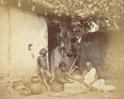 Two women grinding grain in the yard of a house